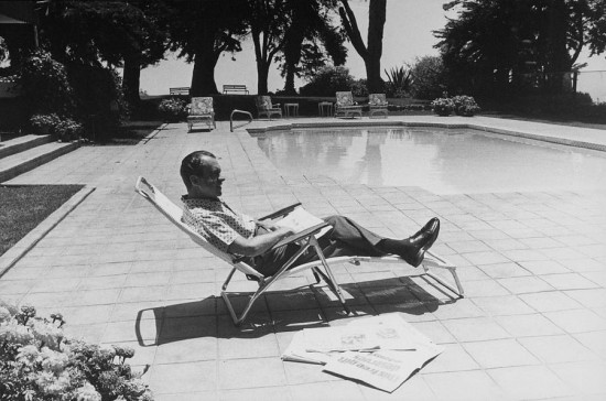 Richard Nixon, at home reading newspapers.